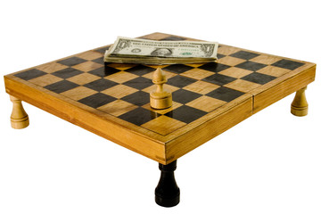 Old chessboard resting upon the rooks, with a pawn and dollars
