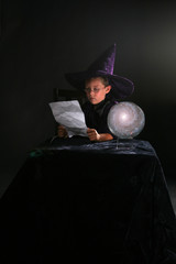 wizard child reading his spell next to a crystal ball