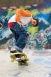cool skater against a graffiti wall