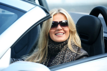 Blond girl in sunglasses driving convertable car