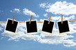Photos hanging on a rope with clothespins against blue sky