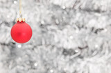 Red Christmas ball ornament over silver garland background