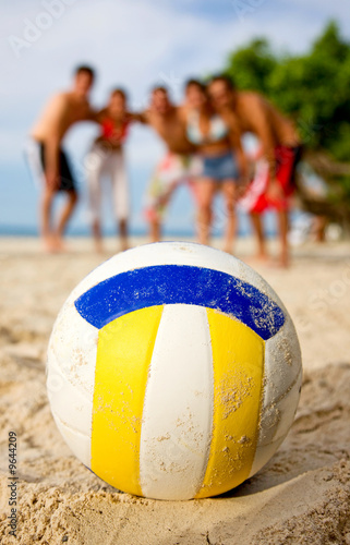 beach volleyball ball at the beach with the team behind