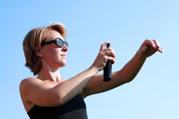 Femme vaporise de la crème solaire