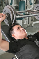 man lifting barbell in fitness center