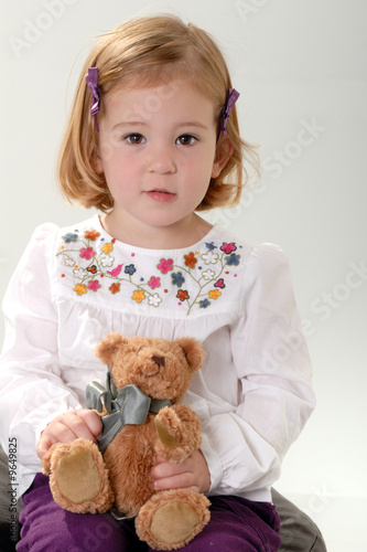 cute two year old blonde toddler poses with teddy