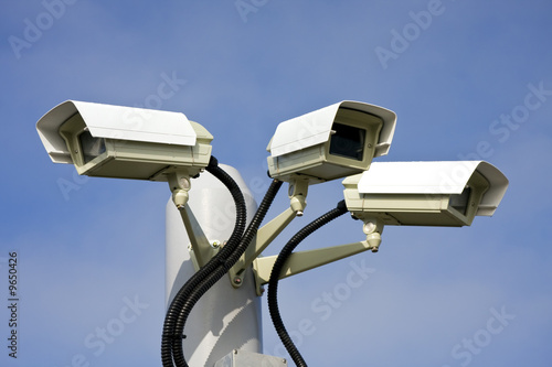 Security cctv cameras in front of blue sky - 9650426