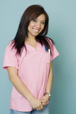 Attractive young woman smiling while wearing pink scrubs poster