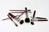 Brown makeup brushes for cheeks, eyes, lips and more, isolated poster