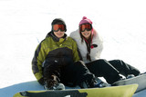 Young happy couple in goggles on snowboards poster