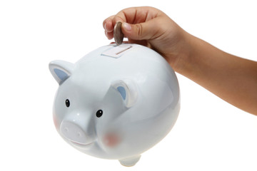 Hand putting money in piggy bank.