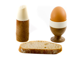 a soft boiled egg, a slice of bread and a saltpot
