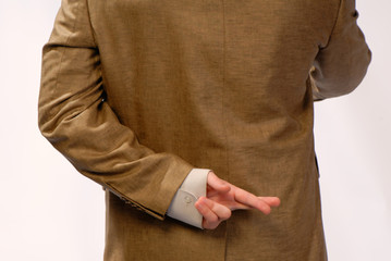 young businessman holds  hand behind  back with  crossed
