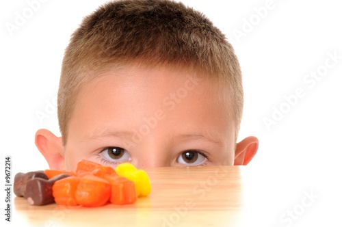 Boy Looking at Halloween Candy isolated on white