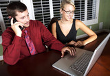 Pretty blond and handsome man staying late at work poster