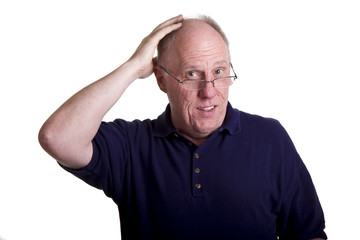 An older man in blue shirt and glasses rubbing his bald head