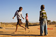 african children jumping rope in the sand,