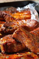 delicious spicy barbeque ribs in roasting tray on foil