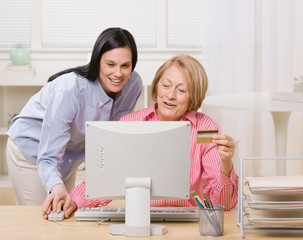 Mother and daughter making online purchase with credit card