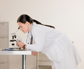 Side view of female doctor examining specimen in microscope