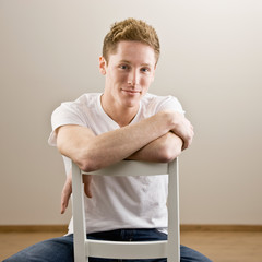 Cool young man sitting backwards in chair