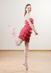 Ballerina in frilly dress and leg warmers balancing on toe