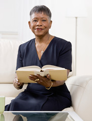 Mature African woman reading book on sofa in livingroom