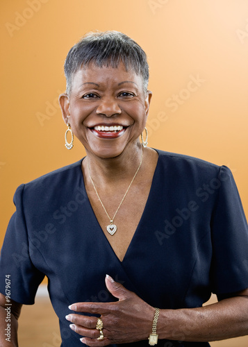 Studio shot of smiling mature African woman with short hair