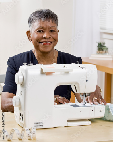 Mature African woman using sewing machine