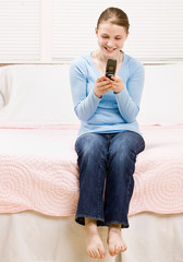 Teenage girl sitting on bed text messaging on cell phone