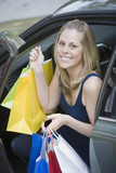 Smiling woman with shopping bags getting out of car