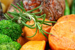 A sprig of rosemary with baked carrots and broccoli.