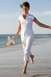 Active and happy senior woman running at the beach poster