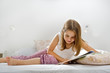 little girl lying on bed reading a book