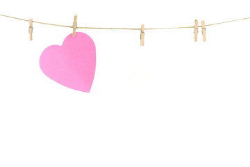 Pink paper heart on a clothes line.