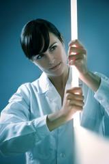 Italian woman holding neon stick in lab.