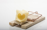 Lovetrap. Heart shaped cheese on mousetrap. Studio shot. poster
