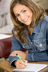 Beautiful girl studying in a classroom - smiling and writting
