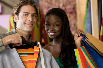 beautiful couple smiling with shopping bags in a mall