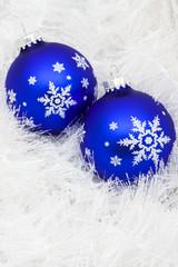 Blue glass ball on white shiny garland making a background