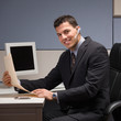 Happy young businessman with headset working in cubicle