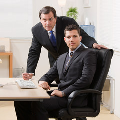 Confident businessmen looking serious at desk in office