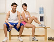 Man and woman holding water bottles in health club