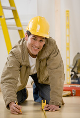 Worker in hard-hat kneeling and using measuring tape