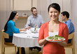 Woman holding appetizer and serving friends at dinner party