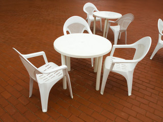 White plastic little tables in summer cafe.