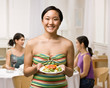 Woman holding salad about to join friends for dinner party