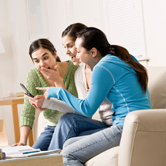 Friends pointing and reading text message on cell phone