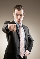 Authoritative, serious businessman pointing accusing finger