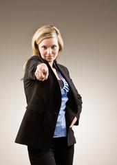 Authoritative, serious businesswoman pointing accusing finger